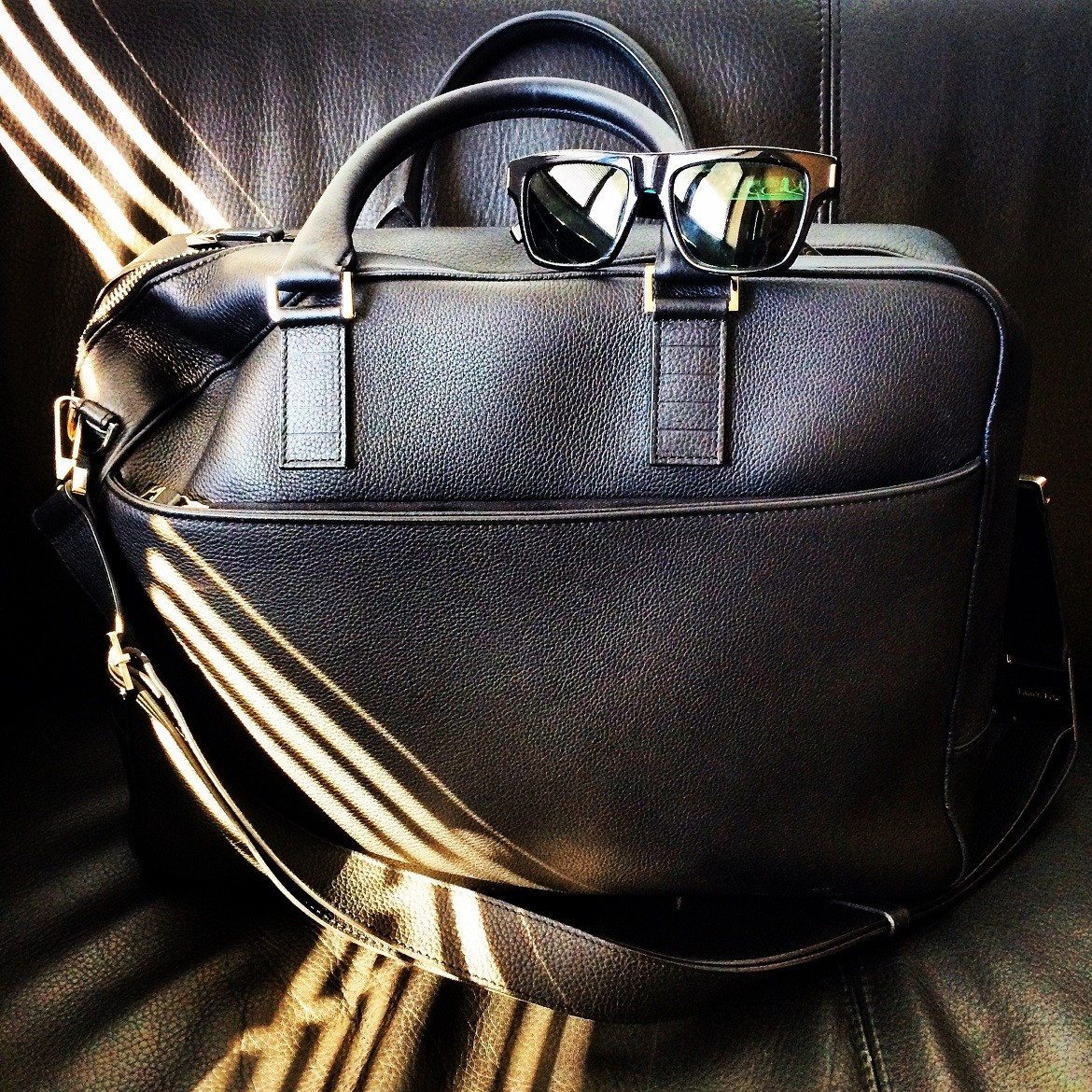Leather on leather, black on black - Briefcase by DIOR HOMME. Sunglasses by SAINT LAURENT by Hedi Slimane.