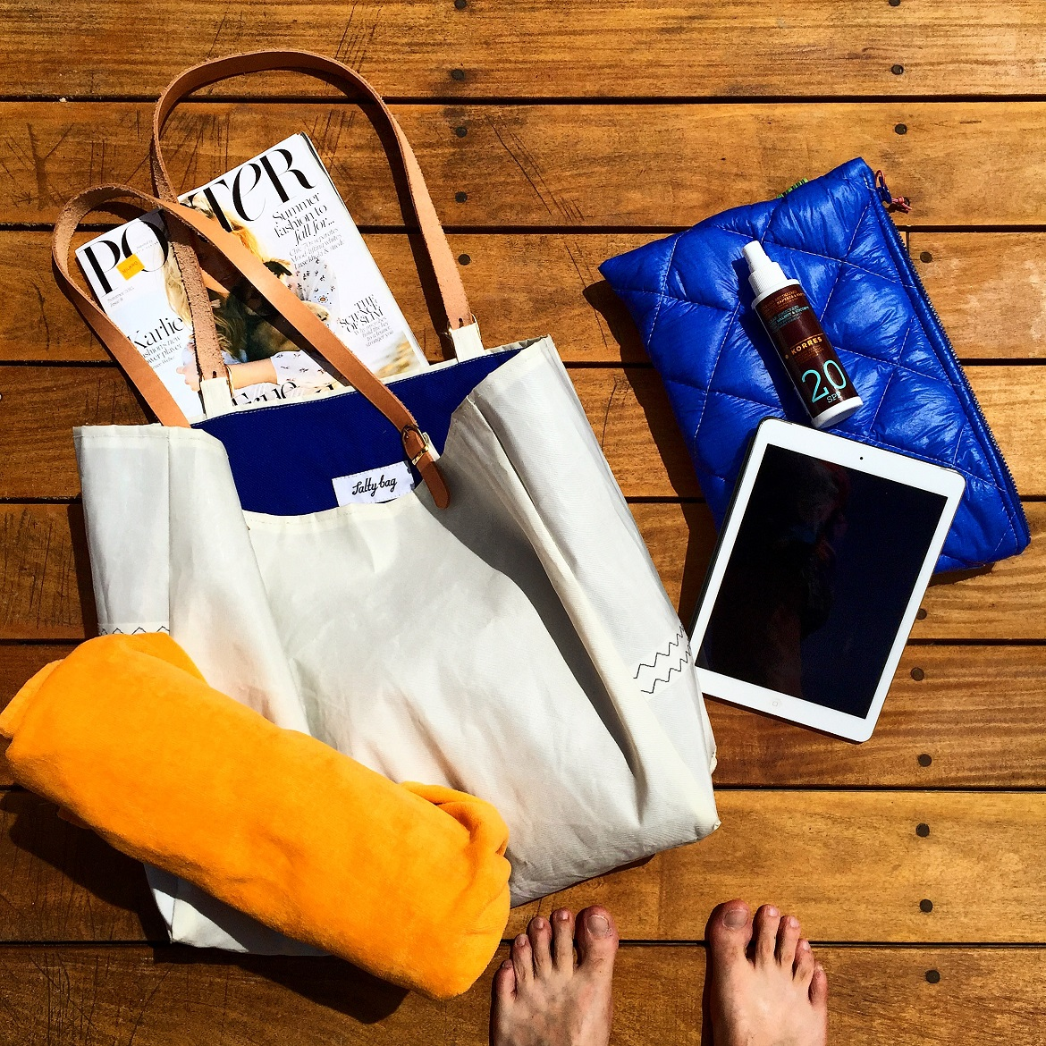 "On the deck: holdall Salty Bag ""Armathea"", clutch Salty Bag ""Atokos R2R"", sunscreen SPF20 by Korres Natural Products, Porter magazine, iPad & Nikki Beach towel"